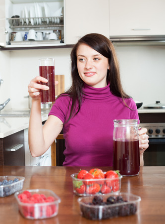 girl with fresh berries beverage in glass at home kitchen  photo
