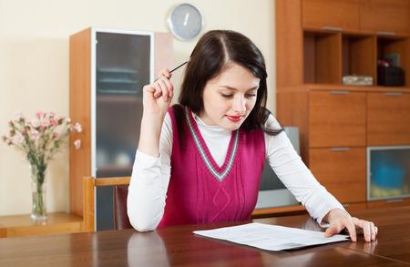 utility payments: serious woman reading document at home