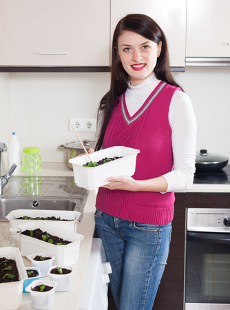 Happy woman with  seedlings at home kitchen photo