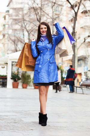 Smiling girl with shopping bags at street photo