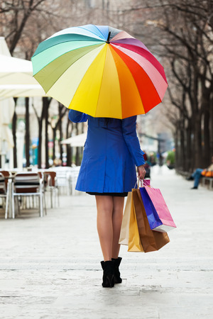 Rear view of woman with purchases and umbrella at street photo
