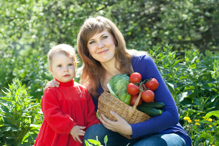 Happy woman and baby girl with vegetables harvest in garden photo