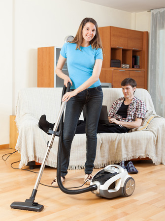 Smile woman cleaning with vaccuumcleaner at home while young man with notebook resting photo