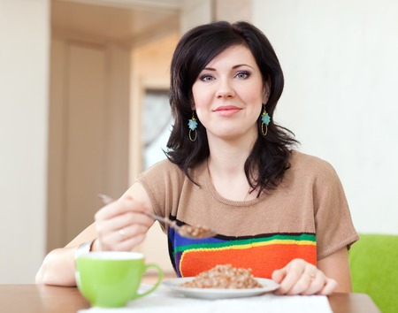 kasha: Pretty woman eats buckwheat cereal at home Stock Photo