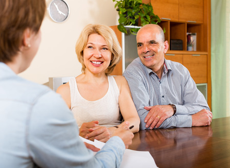 social worker: Smiling mature couple listening worker of the company Stock Photo