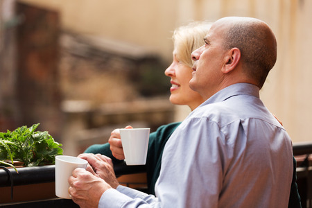 Happy mature couple discussing and drinking tea at balcony  photo