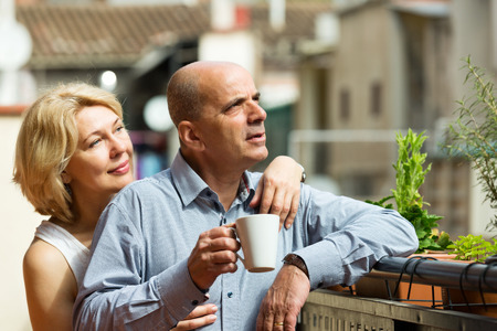 Happy mature couple having morning coffee at balcony photo