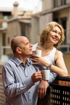 Elderly  couple having morning coffee at balcony  photo