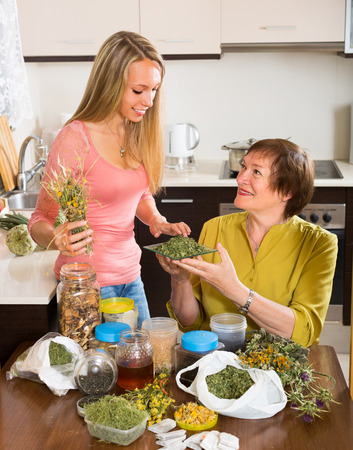 Smiling mother and adult daughter with herbal tea and herbs at the table  photo
