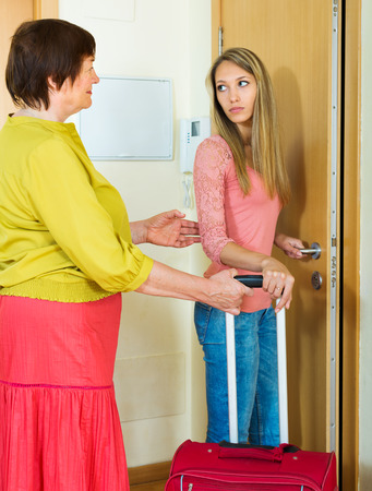 lodger: Upset adult daughter with suitcase leaving apartment of mother  Stock Photo