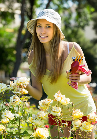 Smiling girl in t-short and panama hat in the garden in sunny day  photo