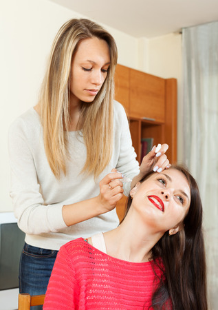 nosotrophy: Woman  dripping eardrops to girlfriend in home Stock Photo