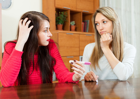 woman comforting depressed friend with pregnancy test at  home  photo