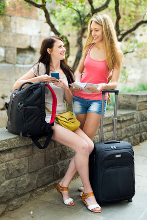 navigator: Two happy girls on vacation with baggage and navigator Stock Photo