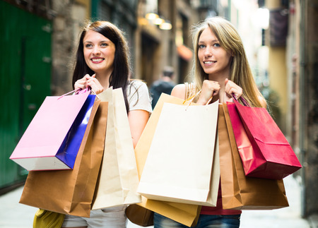 Two happy young girl going shopping in European city photo
