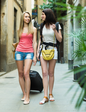 Two young women with luggage walking through city street photo