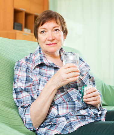 Tired female pensioner with pills and glass of water at home photo