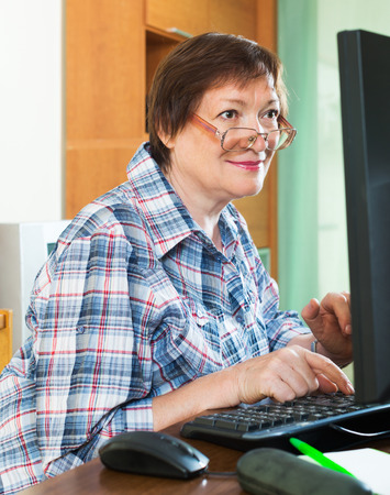 Happy female pensioner studying computer literacy in office interior photo