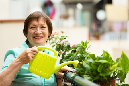 Portrait of mature housewife watering domestic plants on terrace photo