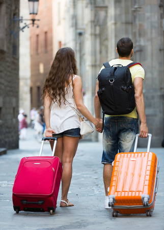 Tourist couple with baggage heading to hotel on foot  photo