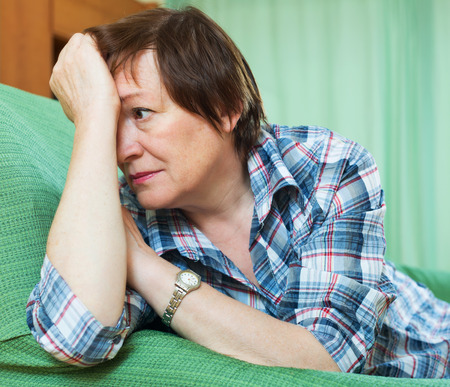 Stressed elderly woman laying on her elbows and thinking indoor photo
