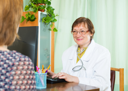 communicates: Mature doctor  communicates with patient sitting at PC Stock Photo