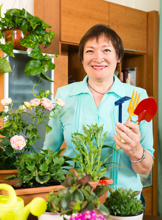 mature woman working with fresh flowers in pots at home photo
