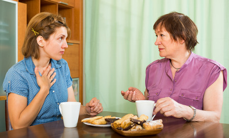 Senior woman with young daughter drinking tea at the table and talking photo