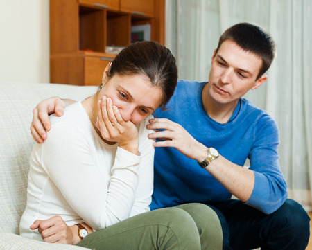 fracas: crying woman, man consoling her on sofa at home