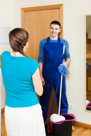 houseman: Woman meeting smiling cleaner at the door at home Stock Photo