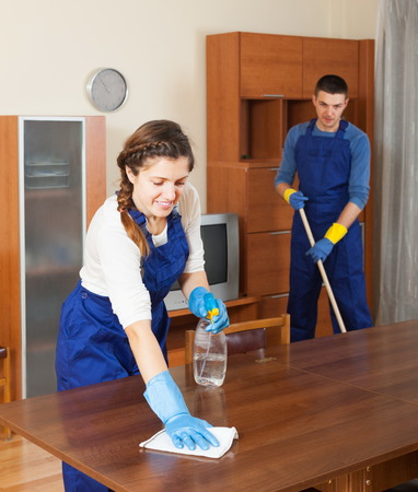Professional cleaners dusting wooden furiture at living room photo