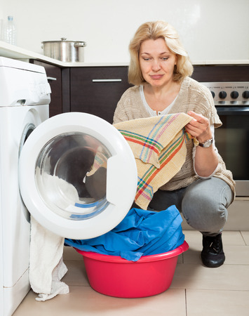 Home laundry. Unhappy  woman using washing machine at home photo