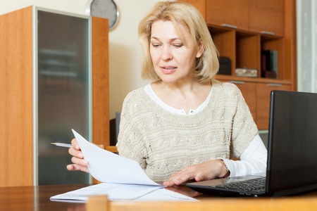 60 something: Serious mature woman staring financial documents with laptop  at table in home Stock Photo