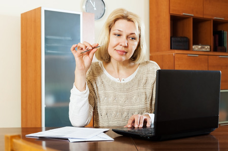 60 something: serious mature woman with notebook and documents at table at home   Stock Photo