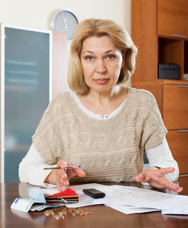 parsimony: Sad mature woman thinking about the financial issue at  home Stock Photo