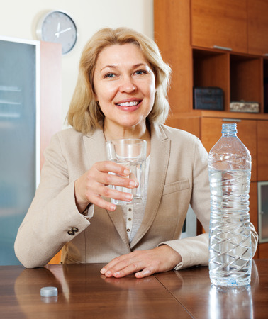 Blonde mature woman drinking water from glass photo