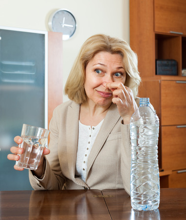 addle: Sad mature woman with grass of poor quality water  at home Stock Photo