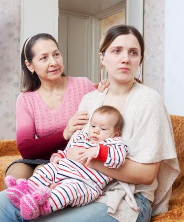 problemas familiares: Problemas femeninos de la familia. Madre madura pide perd�n a la hija adulta con el beb� despu�s de la pelea en el hogar