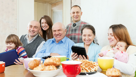 Happy family of three generations with electronic devices over tea in living room at home photo