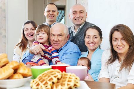 Portrait of  large joyful three generations family sits on sofa in livingroom  photo