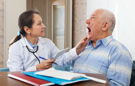 Female mature doctor looks the throat of senior patient in clinic photo