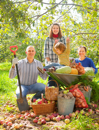 Happy  family with vegetables harvest in garden Stock Photo - 29787449