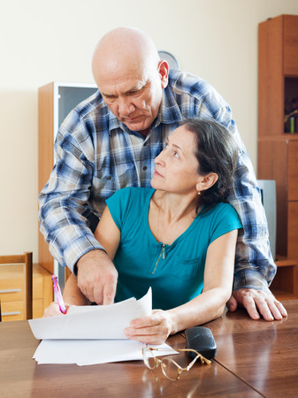serious mature woman fills documents, senior man helping her at home photo