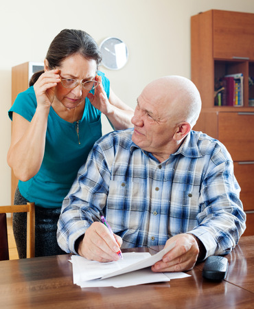 parsimony: Smiling mature couple reading financial documents in home   Stock Photo