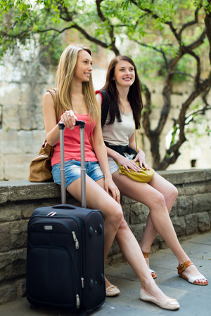 Two young girls on vacation with baggage on street photo