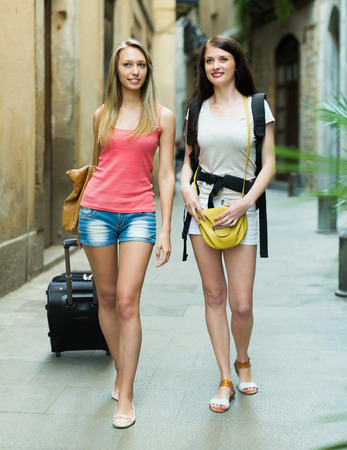 Two happy young women with luggage walking through city street photo