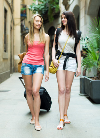 Two young travelers smiling with baggage and heading to hotel on foot photo
