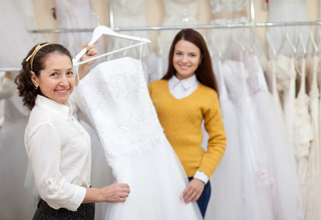 bridal salon: Shop assistant  helps the bride in choosing bridal dress at shop of wedding fashion. Focus on mature