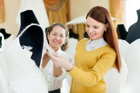 bridal gown: Amistoso tienda consultan ayuda a la novia en la elecci�n de vestido de novia en la tienda de moda de la boda. Centrarse en las ni�as