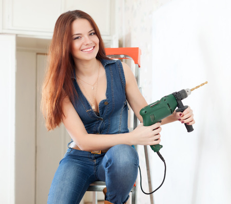 Happy girl in overalls with drill on stepladder in the interior photo